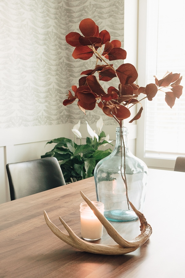 mason jar candles on a table with a vase of flowers
