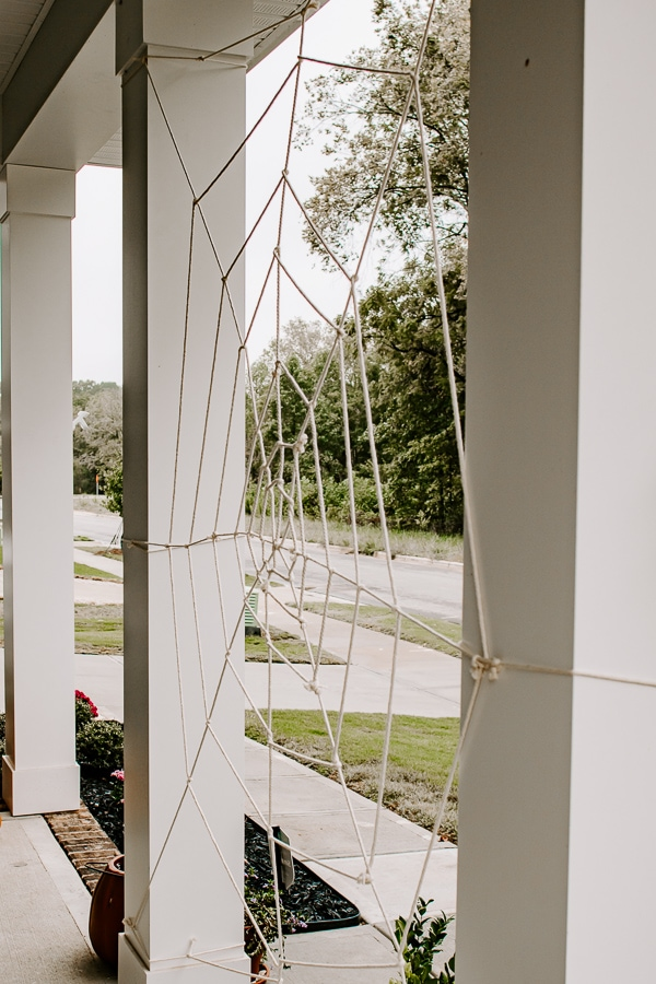 a giant spider web between porch posts