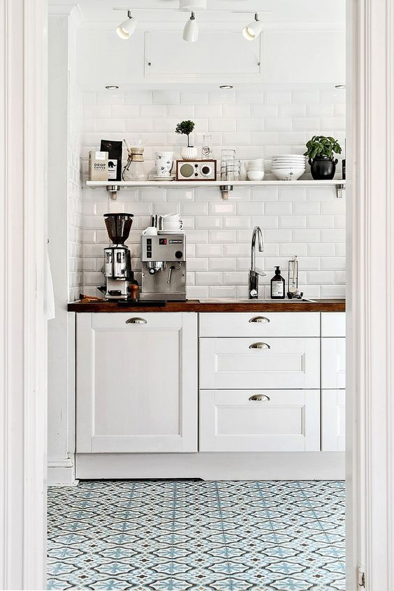 white kitchen cabinets with a wood top and coffee maker