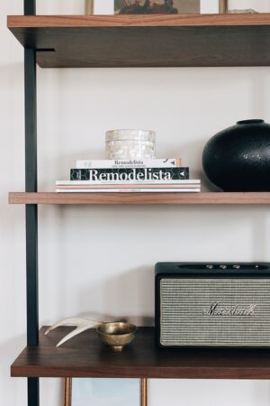 a stack of books with a vase and speaker on a etagere bookshelf