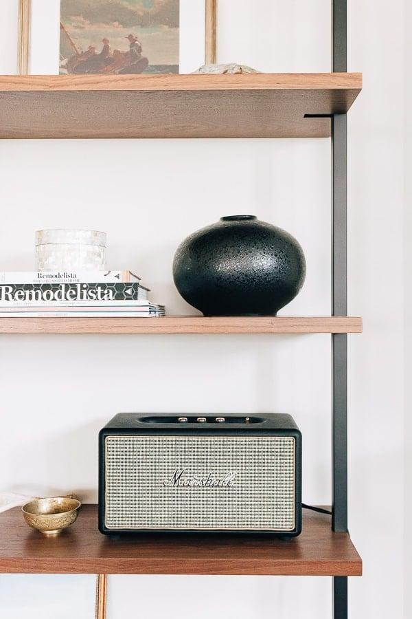 a black vase and speaker on a bookshelf