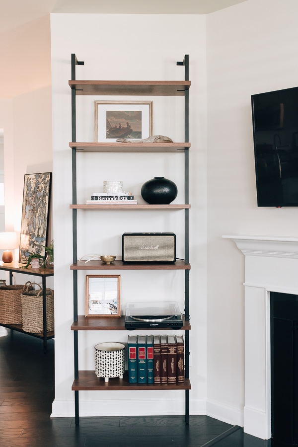 a tall etagere bookshelf on the wall