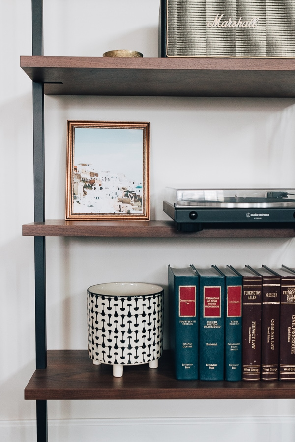 bookshelf with books and a picture and vase