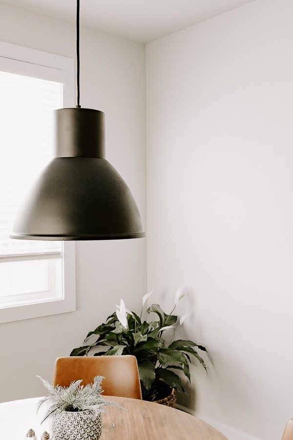 black spray painted light fixture over a table, with a plant in the background