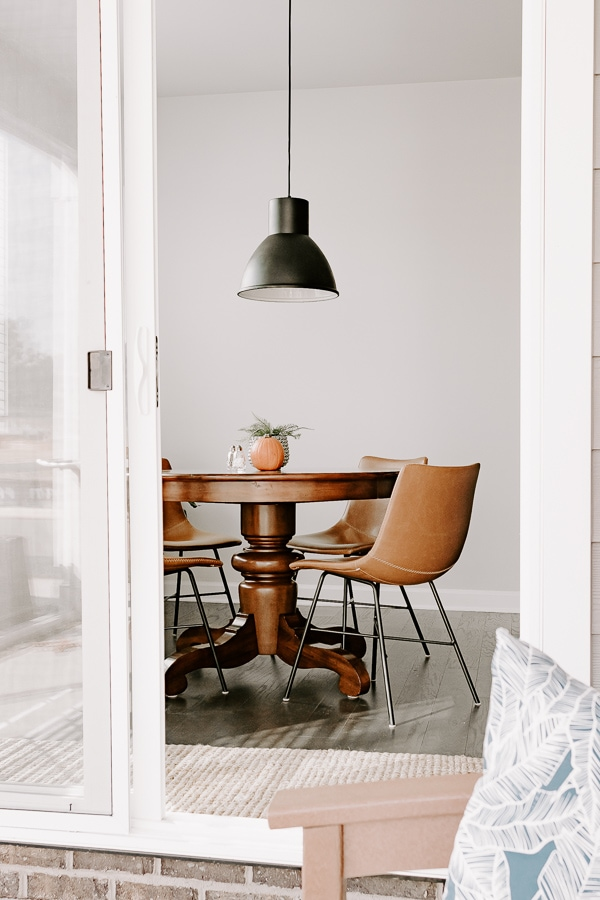 black pendant light in a breakfast nook, plant and leather chairs