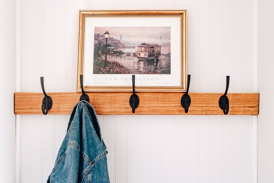 view of coat hooks with jean jacket hanging and photo on top