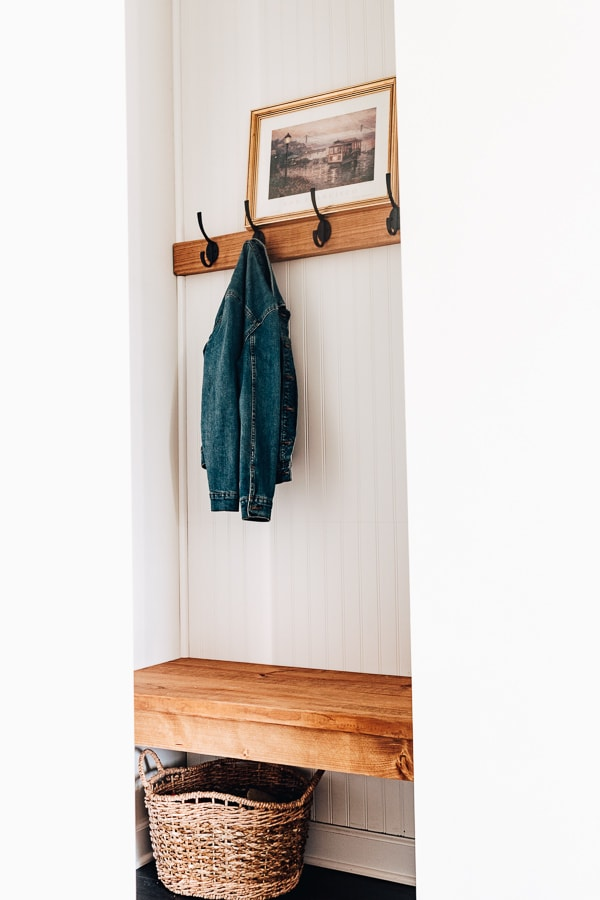 diy mudroom bench with jean jacket hanging and photo