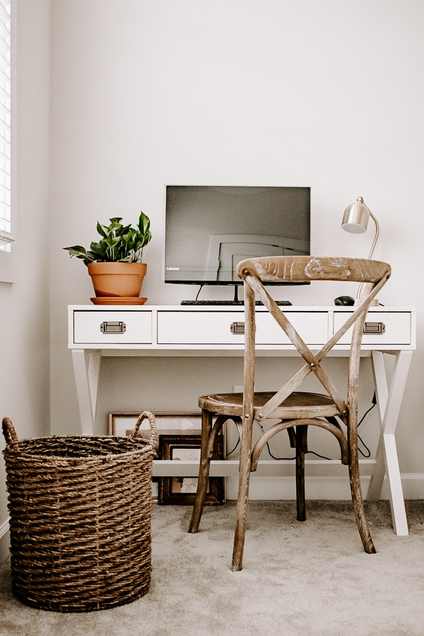white desk area with basket and potted plant and computer. vintage chair
