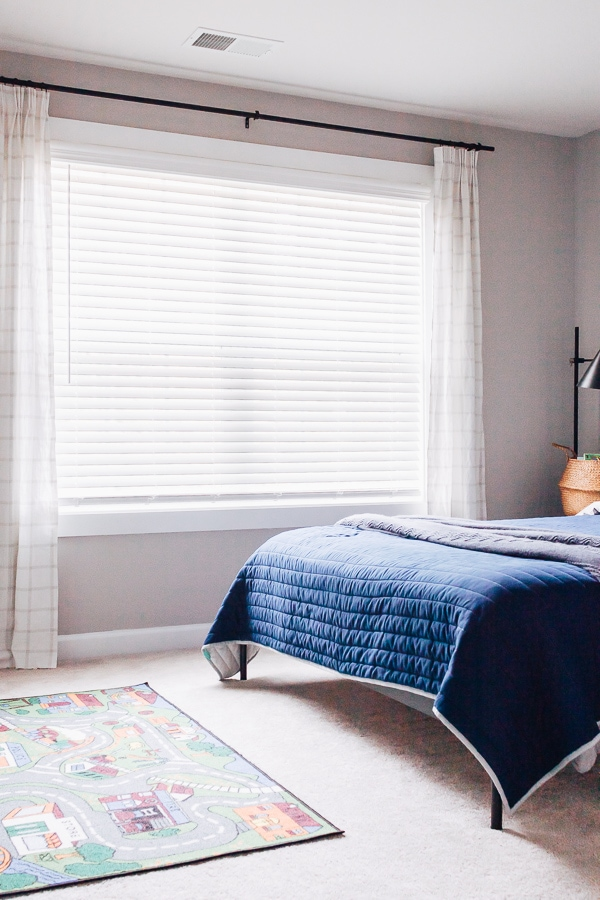 boys room with navy bedspread and ivory and gray curtains
