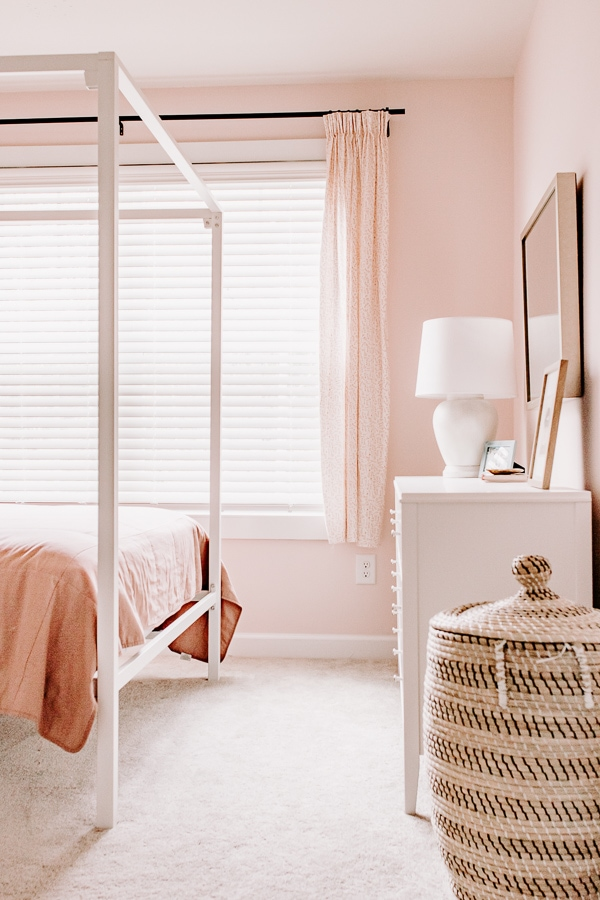 pink girls room with basket, white lamp and dresser and pinch pleat curtains