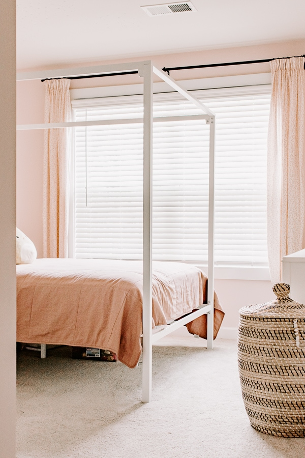 pink bedroom with pink bedding, pink walls and pink pinch pleat curtains