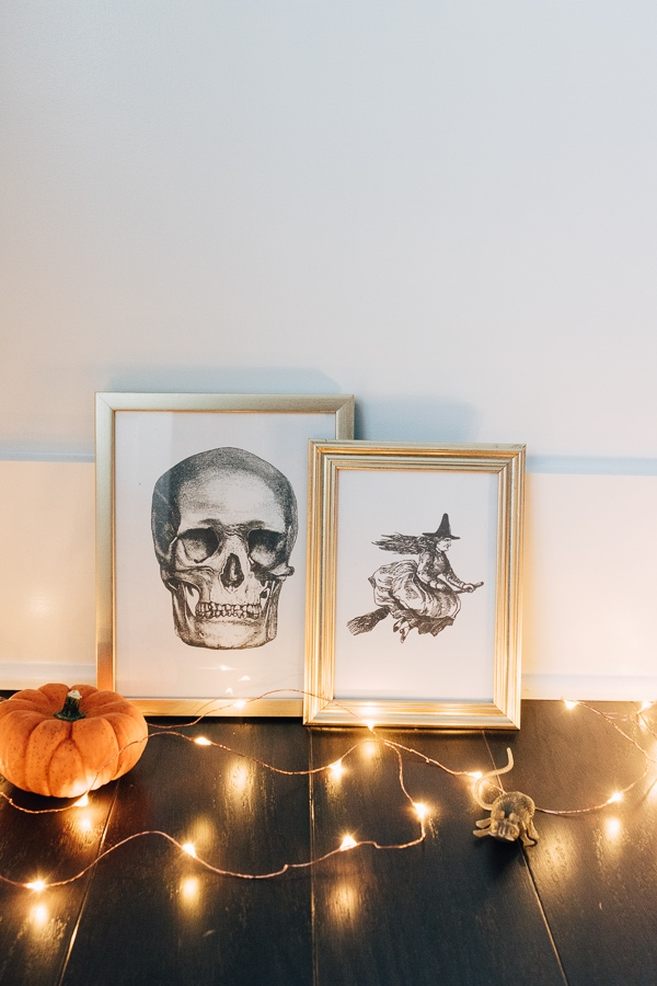 skull and witch wall art in gold frames with fairy lights