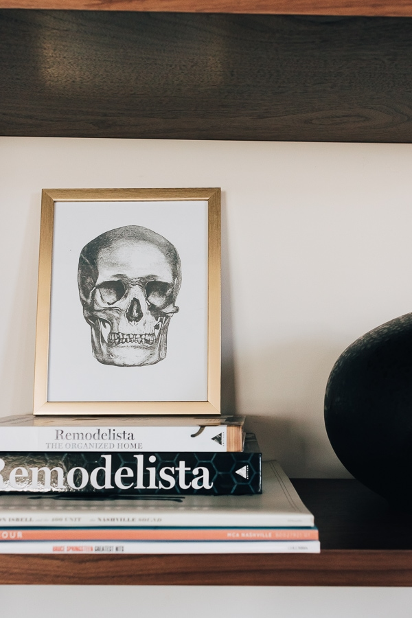 skull picture in a gold frame on a bookshelf