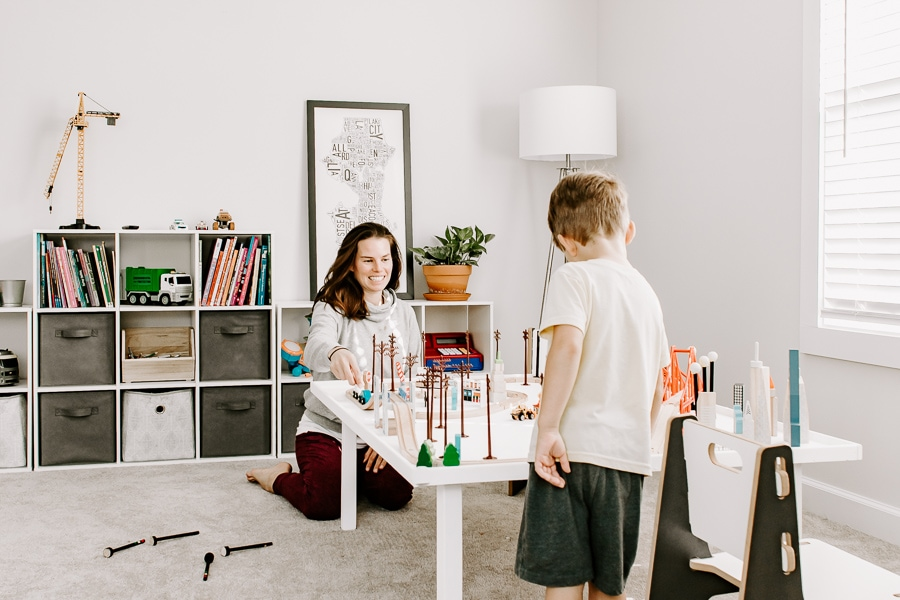 little boy and mom playing tracks on a activity table