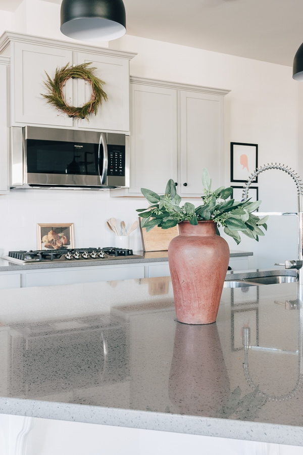 kitchen with wreath hanging a vase with greenery on island and art print behind stove