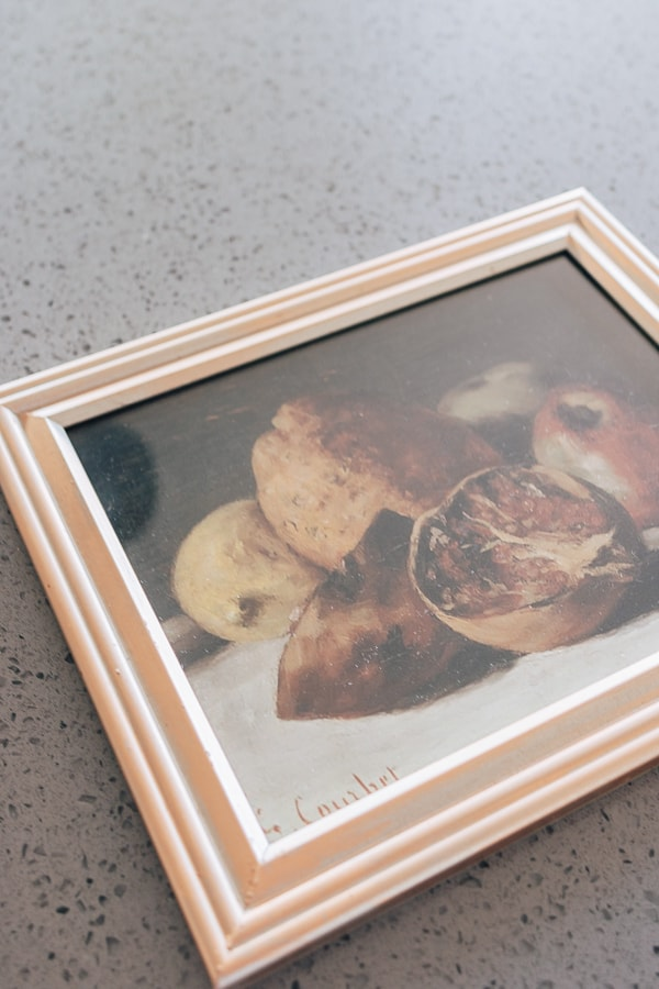 close up of a vintage pear painting framed in a gold frame