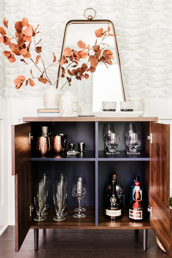 bar cabinet open with glassware and liquor inside