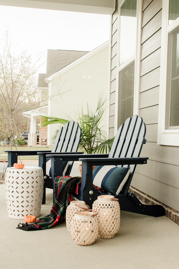 Outdoor porch with adirondack chairs and lanterns from Rooms To Go.