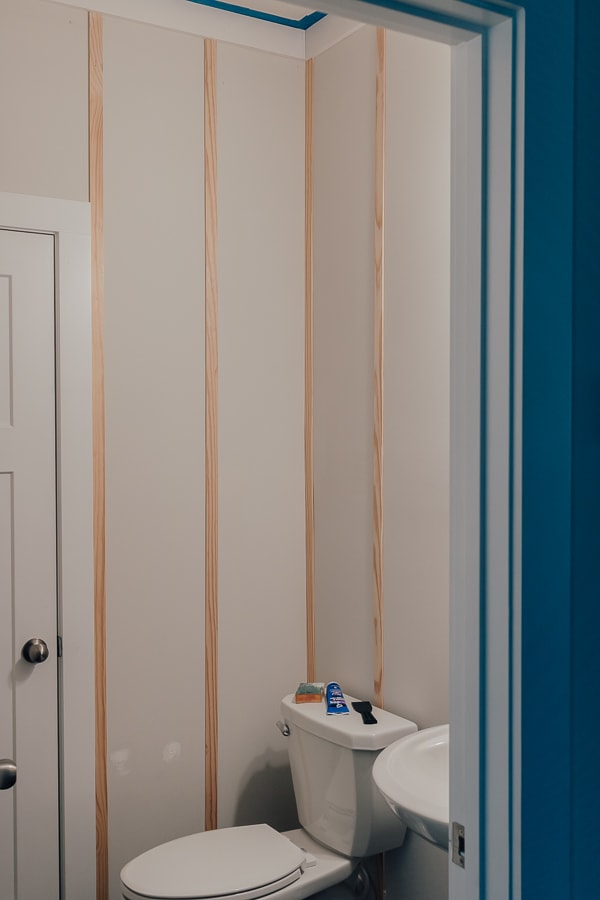 DIY Board and Batten Wall - This post will show you how to install a DIY board and batten wall.  See how we took a boring builder-grade powder room and updated it with a full wall of simple board and batten.