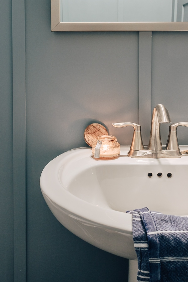 close up of a pedestal sink in a blue bathroom with a lit candle on it and blue hand towel