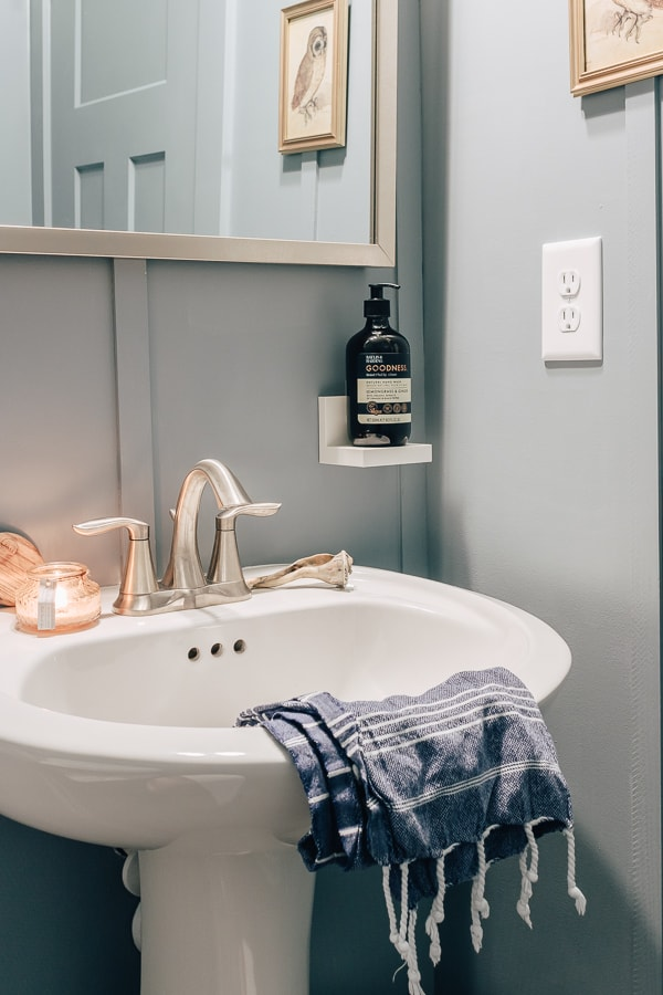 a photo of a pedestal sink with a lit candle and a white ledge for soap