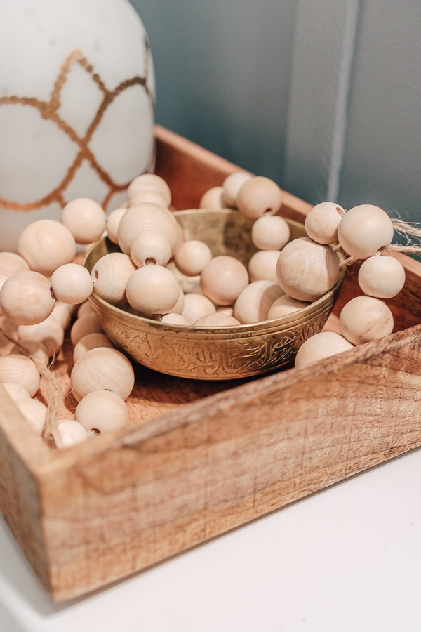 close up of wood beads in a tank tray, home decor bathroom