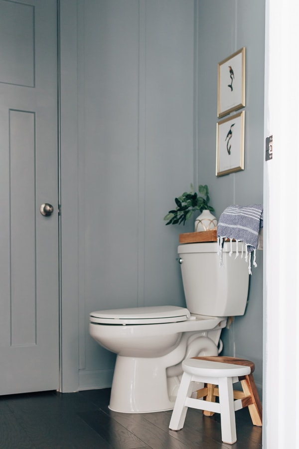board and batten full wall powder room, with a white and wood stool, a tank tray with decor, photos hanging on the wall, dark hardwood floors