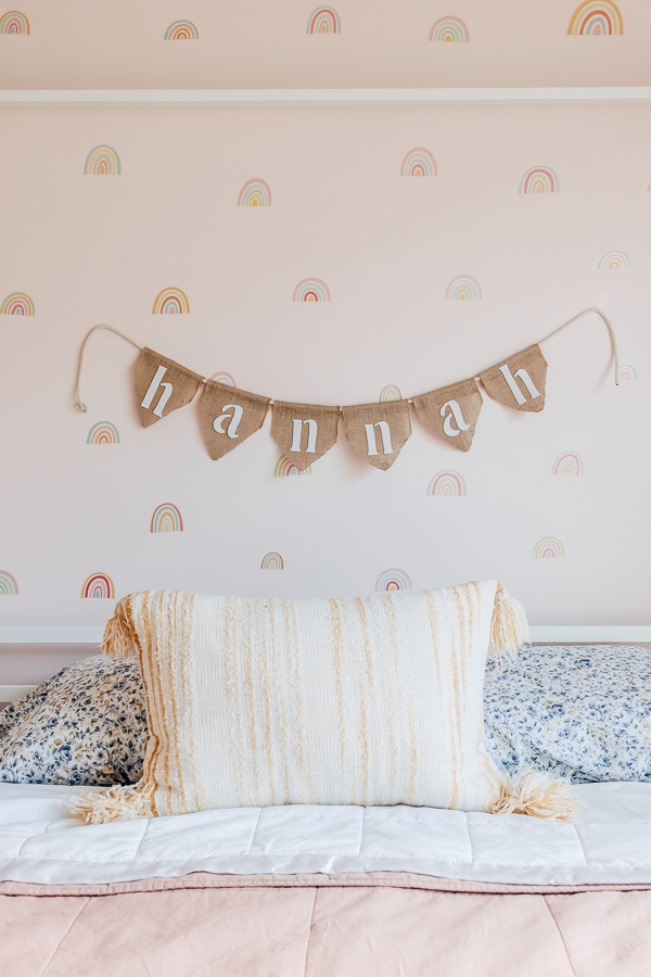 DIY burlap banner with a kids name in white lettering felt hanging behind a bed