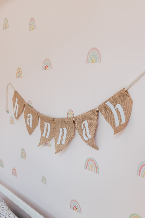 close up of a DIY burlap banner with a kids name hanging behind a bed