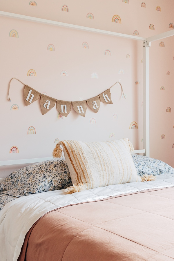 DIY burlap banner with a kids name hanging behind a bed