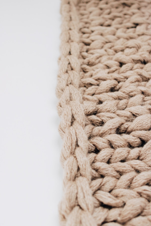 a close up of a chunky knit blanket, tan/beige colored with white background