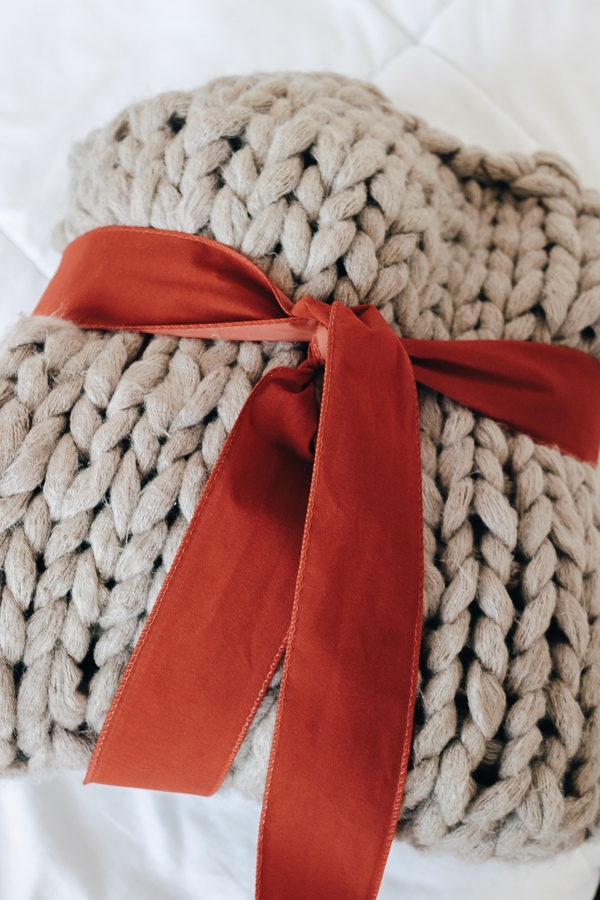 a large chunky knit blanket wrapped in a bow