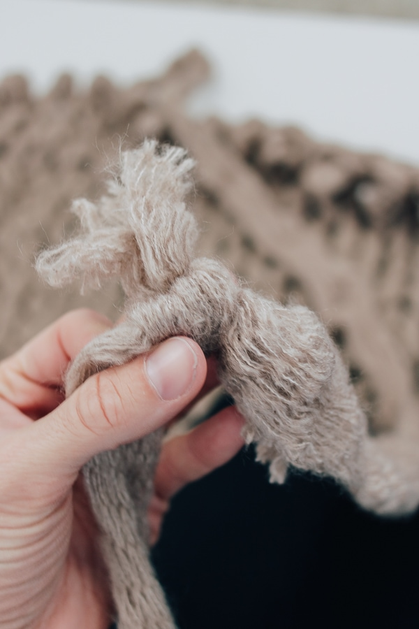 a knot in a chunky knit blanket, camel colored