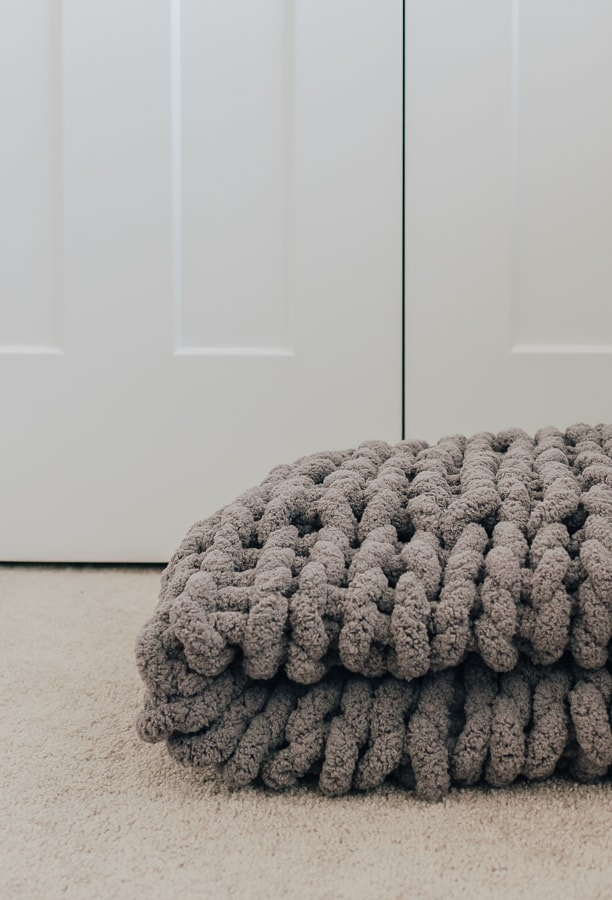 a gray chunky knit blankets folded in half laying on the floor