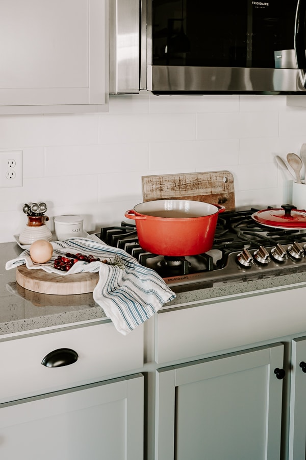 a kitchen with a red pot on the stove and a tea towel next to it with a wood cutting board