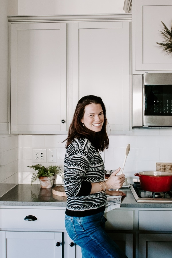 girl standing laughing with a wooden spoon in her hand, wearing a black and white sweater in a kitchen
