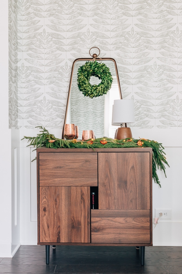 bar cabinet and mirror with wreath and garland on it and copper wine glasses