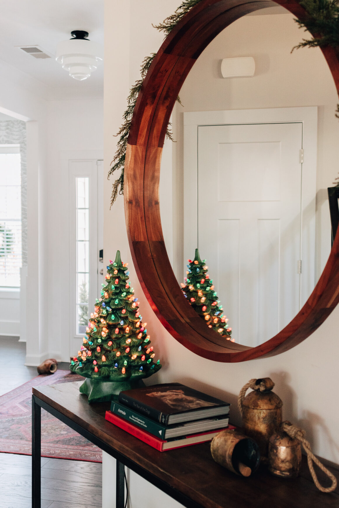 ceramic christmas tree on a table with a large wood mirror and garland hanging over the mirror