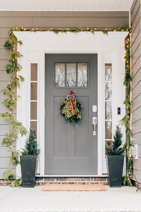 front door decorated for holidays with garland, lights, cedar trees and swag