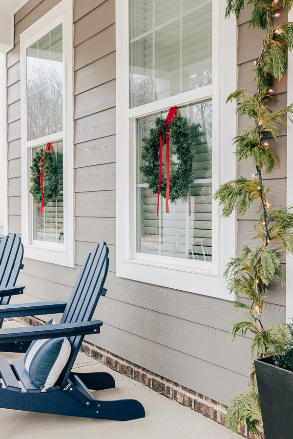 wreaths with red ribbon hanging in windows and blue adirondack chairs