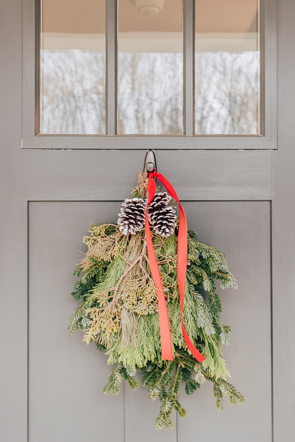christmas swag on front door with red ribbon