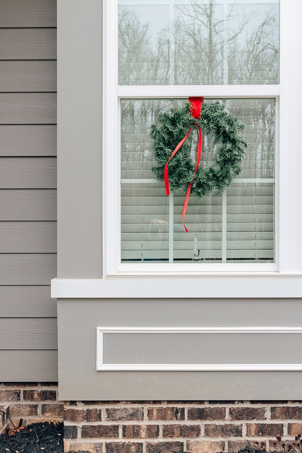 wreath with red ribbon hanging on window