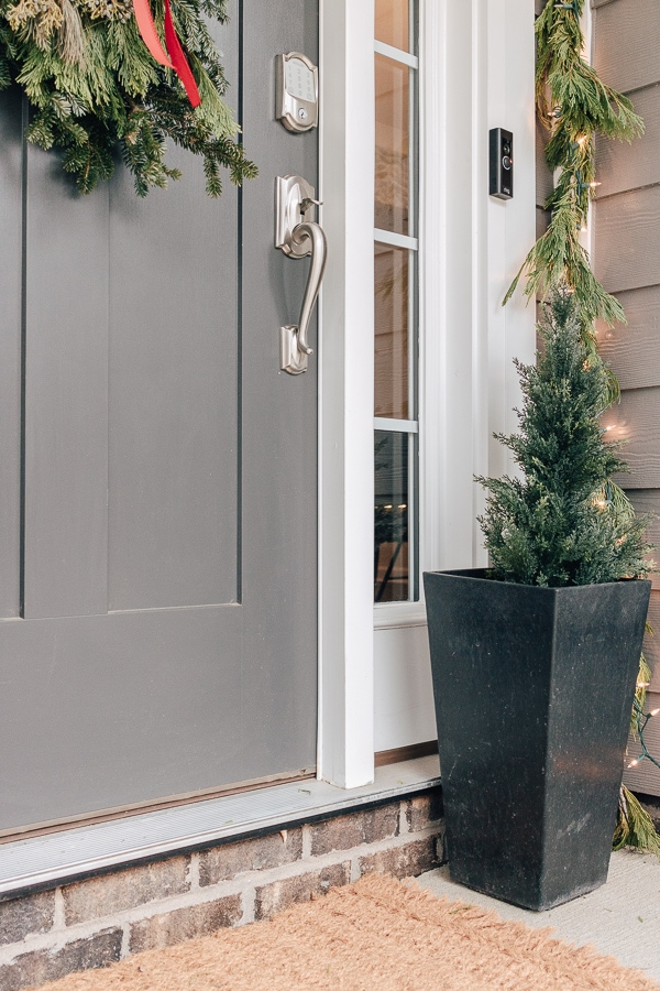 tan doormat with cedar trees in black pots