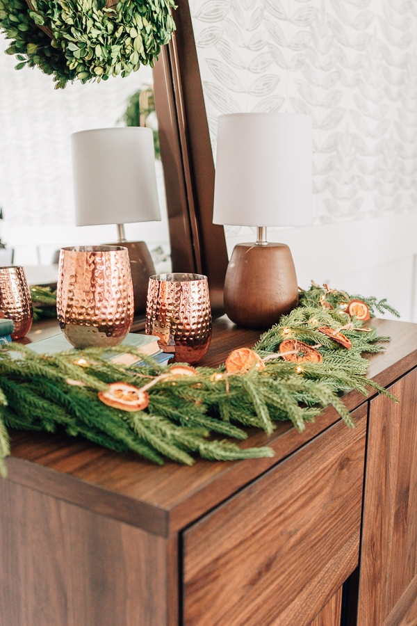 close up of a bar cabinet with garland and a lamp and copper wine glasses