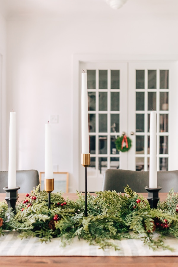 french doors in the background of a dining table with garland and candles