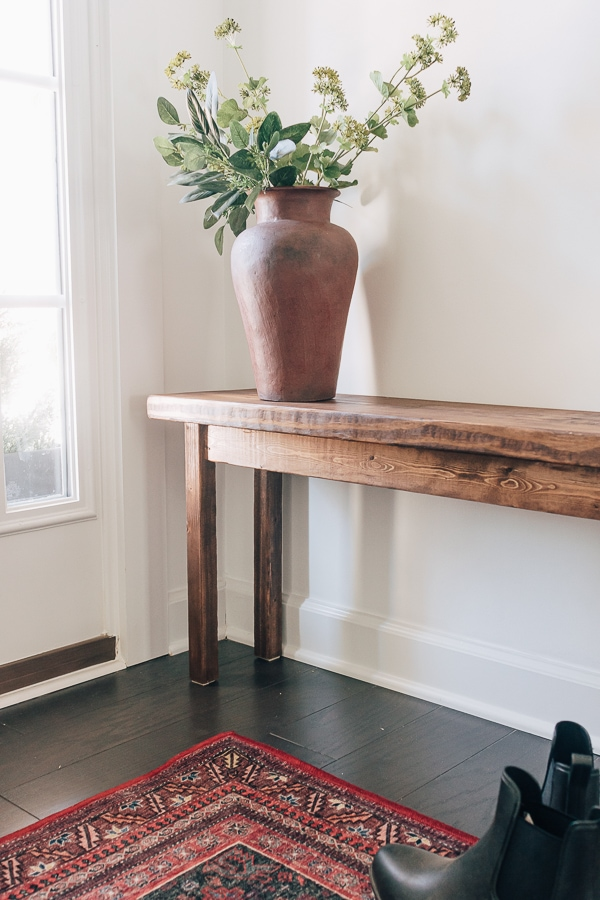 a wood bench with a red rug, black shoes and a vase of flowers