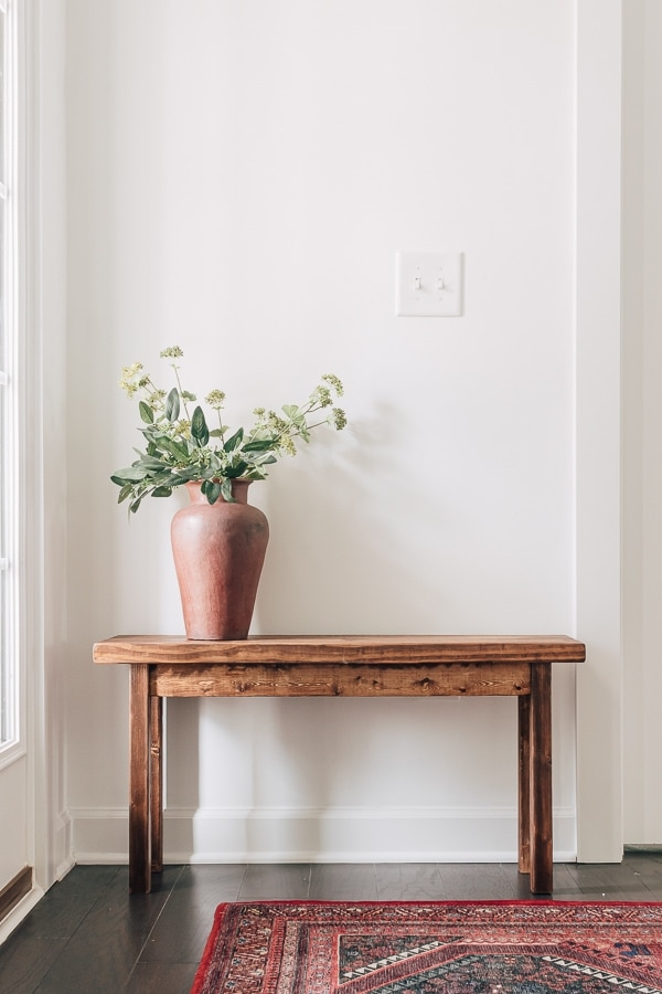 a wood bench in a foyer with white walls, there is a red vase of flowers on top and a red patterned rug