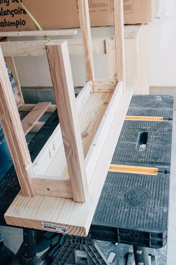 how to make a simple wood bench, showing the bench upside down for attaching the seat.