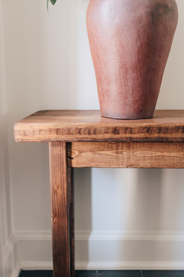 wood bench with a red vase on top