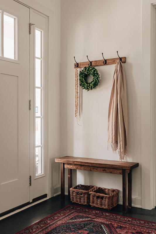 Entryway with a wood bench, small baskets and a coat rack. There is a wreath and shawl hanging from the coat rack.